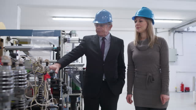 Showing her the production line Boss gives a tour to his new employee exploration stock videos & royalty-free footage