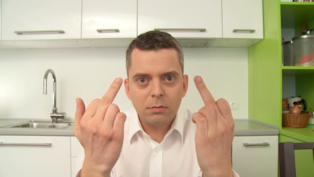 HD: Showing The Middle Finger HD1080p: Front close up view of a middle aged man sitting in his kitchen and looking at the camera while showing his middle finger and getting upset. middle finger stock videos & royalty-free footage