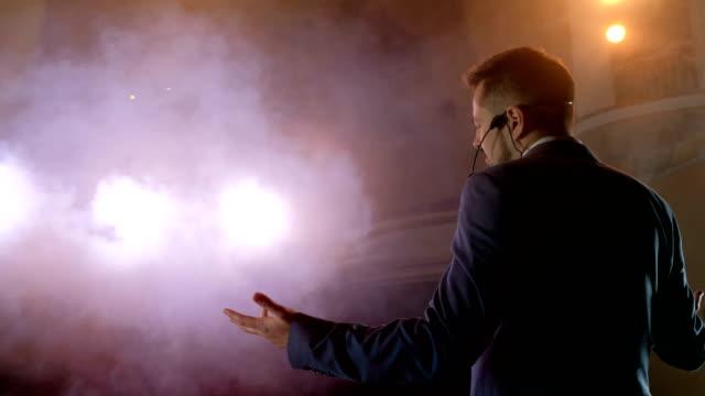 showman. junger männlicher entertainer, moderator oder schauspieler auf der bühne. zurück, arme zu den seiten, rauch auf dem hintergrund des scheinwerfers. - redner stock-videos und b-roll-filmmaterial