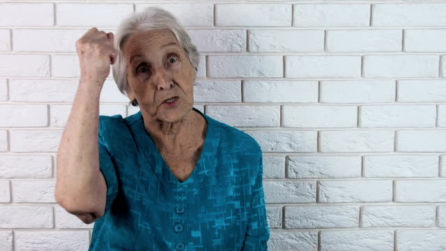 Shows his fist. Aggression of an elderly woman