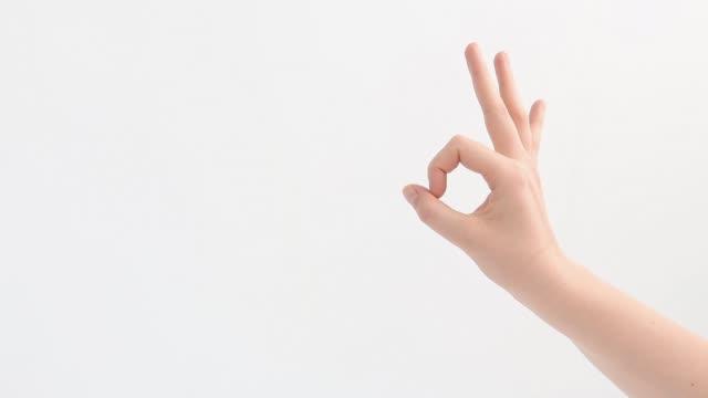 shows ok with right hand, a female hand on a white background. - znak ok filmów i materiałów b-roll