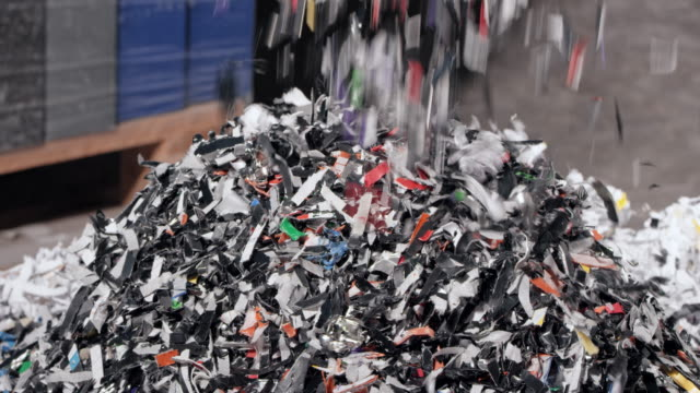 SLO MO Shredded plastic falling down from the conveyor belt Slow motion medium locked down shot of bits of shredded plastic falling on a pile from a conveyor belt of the shredder. Shot in Slovenia. recycling stock videos & royalty-free footage