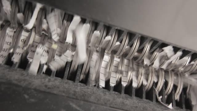 Shredder Cutting Paper From Below, Camera Pan Right To Left Shredder Cutting Paper From Below While Camera Pans Right To Left, Hot Light Coming Through Shredding Blades identity theft stock videos & royalty-free footage