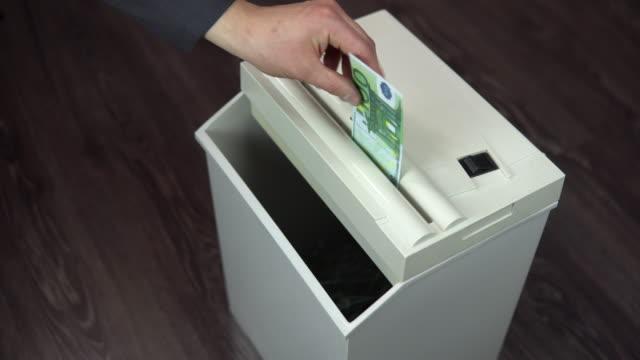 Shredder destroys one hundred euro bill. A man thrusts money into a paper shredder