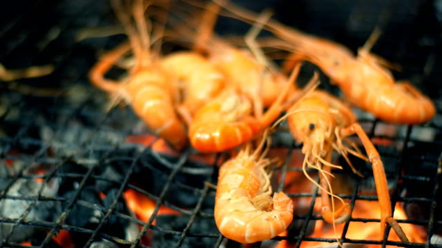 shrimp are grilled and turned over using tongs. night market, pattaya, jomtien. thai cuisine. asian exotic dishes on he market - thai food stock videos and b-roll footage