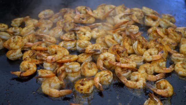 Shrimp. Cook fries shrimps in a large frying pan.