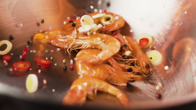 Shrimps with spices and vegetables fall into the wok with a flame, slow motion.