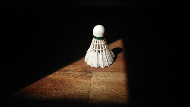 shuttlecock badminton on a wood table in a triengle of light in darknes - badminton stock videos & royalty-free footage