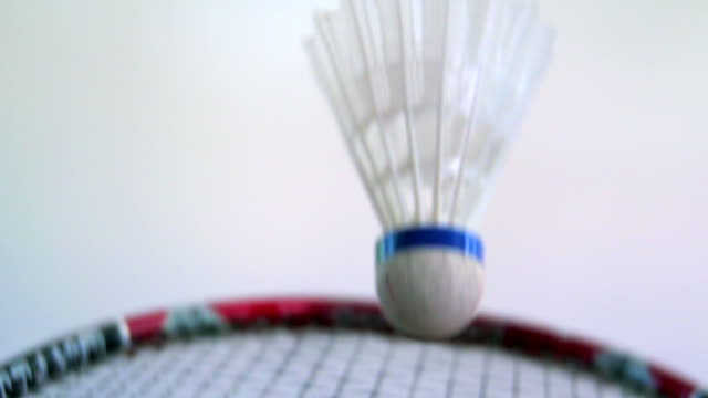 Shuttlecock connecting with a badminton racket on clean white court video