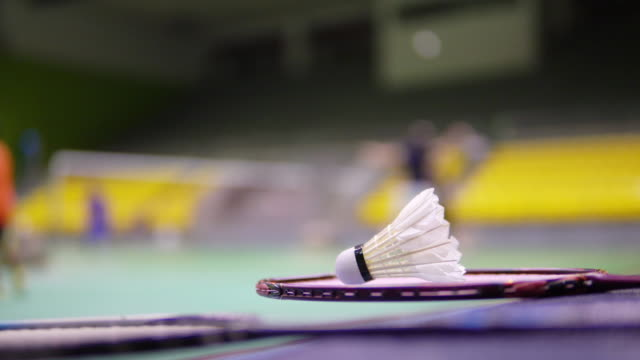 shuttlecocks on badminton court with blurred players. - badminton stock videos & royalty-free footage