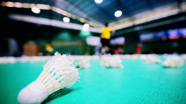 Shuttlecocks on badminton court with blurred players. video