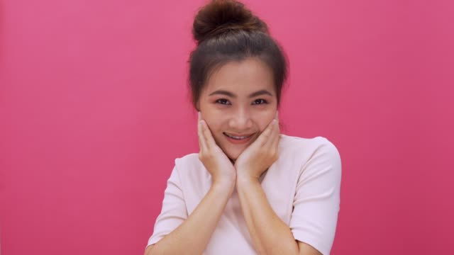Shy acting woman isolated pink background 4k