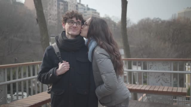 shy caucasian girl in eyeglasses kissing handsome young boy on cheek and smiling at camera. cheerful couple posing in sunny autumn park. love, dating, romance, lifestyle. - brunette woman eyeglasses kiss man video stock e b–roll