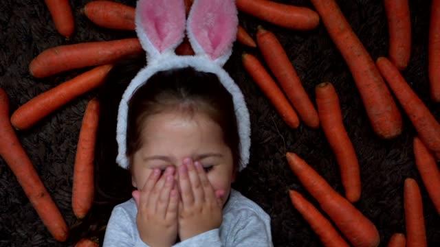 schüchternliches mädchen, das ein kaninchen-ohrkostüm trägt und ihr gesicht mit ihren handflächen bedeckt - karotte peace stock-videos und b-roll-filmmaterial