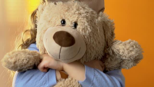 Shy preschool girl hiding behind favorite teddy bear, childhood psychology