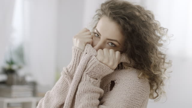 shy woman hiding her face in knitted sweater - donna si nasconde video stock e b–roll