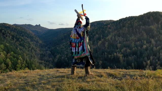 vídeos de stock, filmes e b-roll de xamã siberiano realiza uma dança ritual e bate um pandeiro no topo da montanha. - tradição