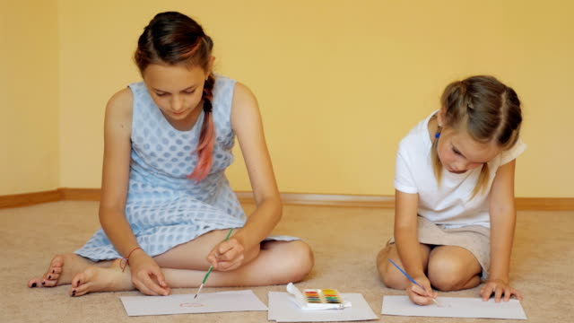Sibling girls drawing with paints Charming sisters sitting on floor with papers and drawing with watercolors at home sister stock videos & royalty-free footage