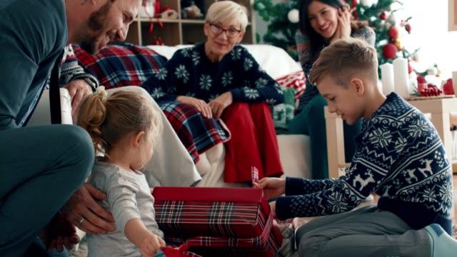 syskon som öppnar sina julklappar medan - christmas gift family bildbanksvideor och videomaterial från bakom kulisserna