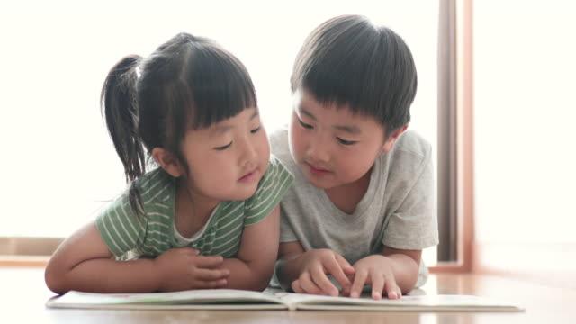 家で本を読む兄弟 - 兄弟姉妹点の映像素材/bロール