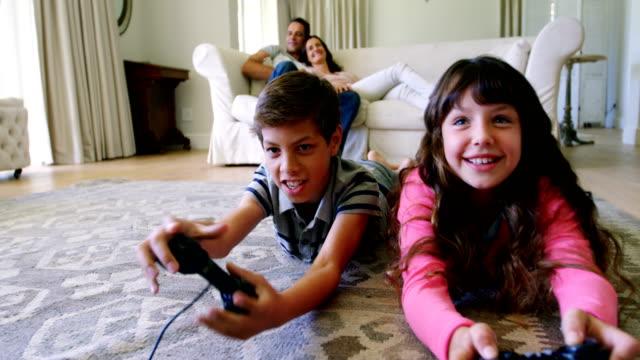 Siblings doing homework while lying on rug in living room video