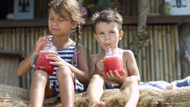 geschwister, die smoothies trinken - tropischer cocktail stock-videos und b-roll-filmmaterial