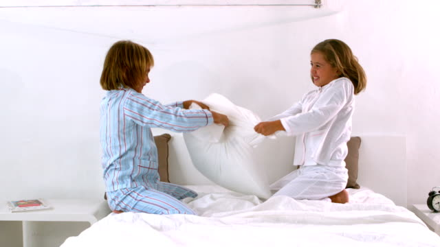 Siblings having a pillow fight on the bed video
