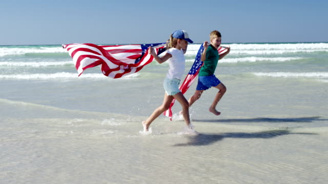 Siblings holding American flag while running on shore at beach video
