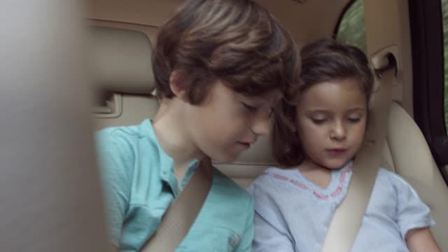 siblings looking at digital tablet in car - preadolescente video stock e b–roll