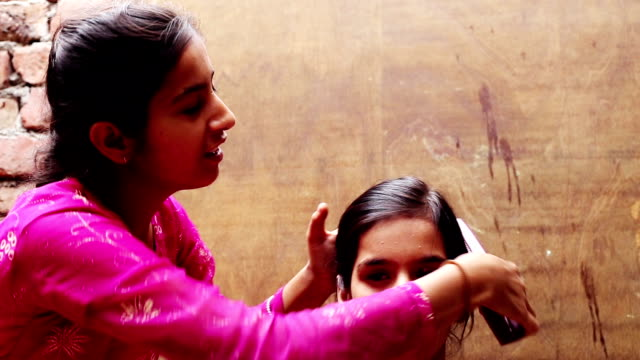 Siblings making ponytail at home - video