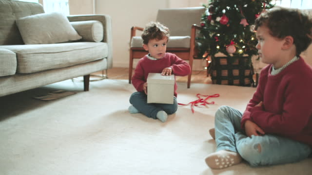 siblings opening the christmas presents. - rivalità video stock e b–roll