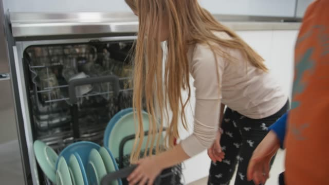 Siblings placing glasses into the dishwasher and closing it