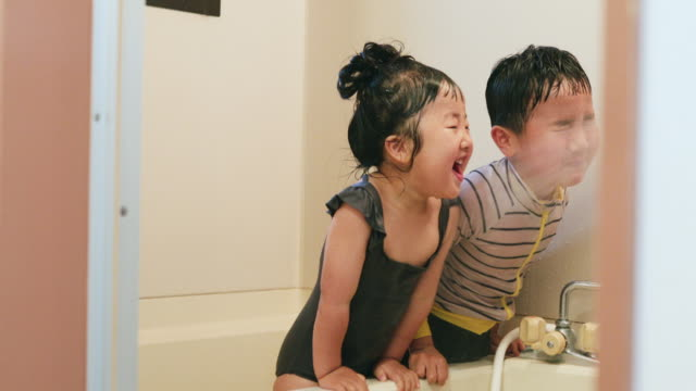 Siblings playing pool in the bathroom Asian brother and sister wearing swim wear and playing in the bathroom at home. Their mother sprinkling water on children's face by shower. real life stock videos & royalty-free footage
