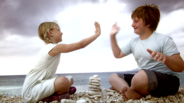 SLO MO Siblings playing with pebbles on the beach video
