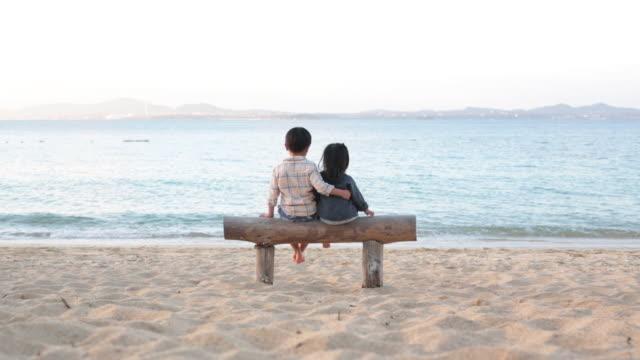 冬はビーチでリラックスしたきょうだい - 兄弟姉妹点の映像素材/bロール