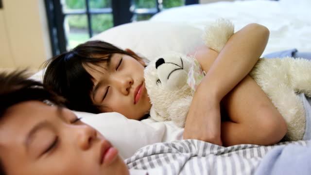 Siblings sleeping on bed in the bed room 4k video