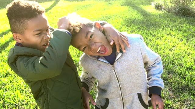 兄弟の笑みを浮かべて、押すと追いやら - 兄弟姉妹点の映像素材/bロール