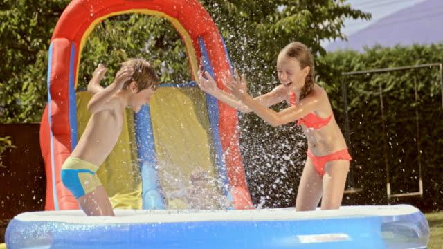 vídeos y material grabado en eventos de stock de cámara lenta hermanos jugando en las colchonetas inflables piscina de agua - backyard pool