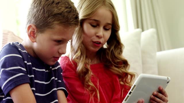 兄弟のリビング ルームでデジタル タブレットを使用して - 姉妹点の映像素材/bロール
