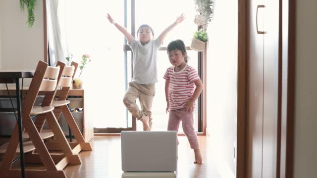 ラップトップを見て、自宅で踊る兄弟 - 兄弟姉妹点の映像素材/bロール