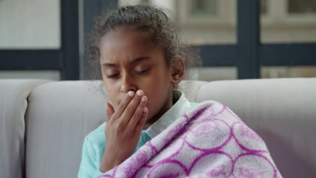 Sick african american girl coughing at home Portrait of cute unwell elementary age african american girl wrapped in warm blanket coughing while resting on sofa at home. Sick child with dry cough, cold and high fever sitting in domestic interior coughing stock videos & royalty-free footage
