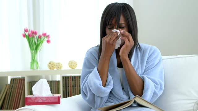 Sick African American woman blowing nose into tissue video