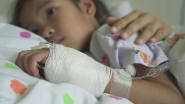 Sick asian child girl with hand bandaged hugging her mother with love in the hospital in slow motion shot video