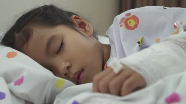Sick asian child girl with hand bandaged is sleeping on bed in the hospital in slow motion shot video