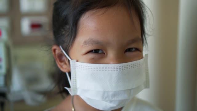 hasta asya küçük çocuk kız giyim koruma maskesi canlı iken yavaş çekimde hastanede - maske stok videoları ve detay görüntü çekimi