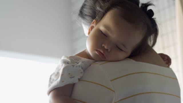 Sick baby girl sleeping on her mother's shoulder