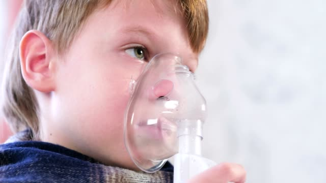 Sick boy inhaling through inhaler mask, nose and lips close-up side view. video