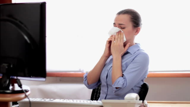 Sick business woman with flu blowing nose in tissue video