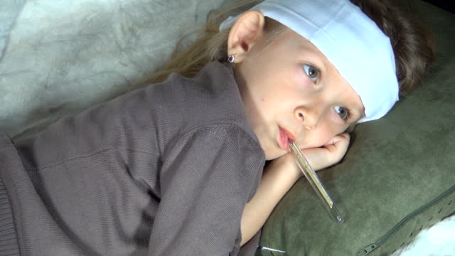 Sick Child on Sofa with Thermometer, Girl Suffering from Cold video