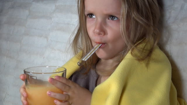 Sick Child with Thermometer and a Glass of Effervescent Vitamins video